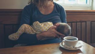Kobieta karmiąca w kawiarni