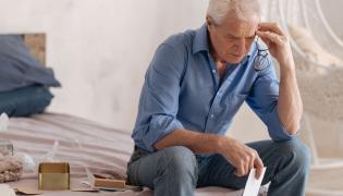 Starszy mężczyzna siedzi zmartwiony