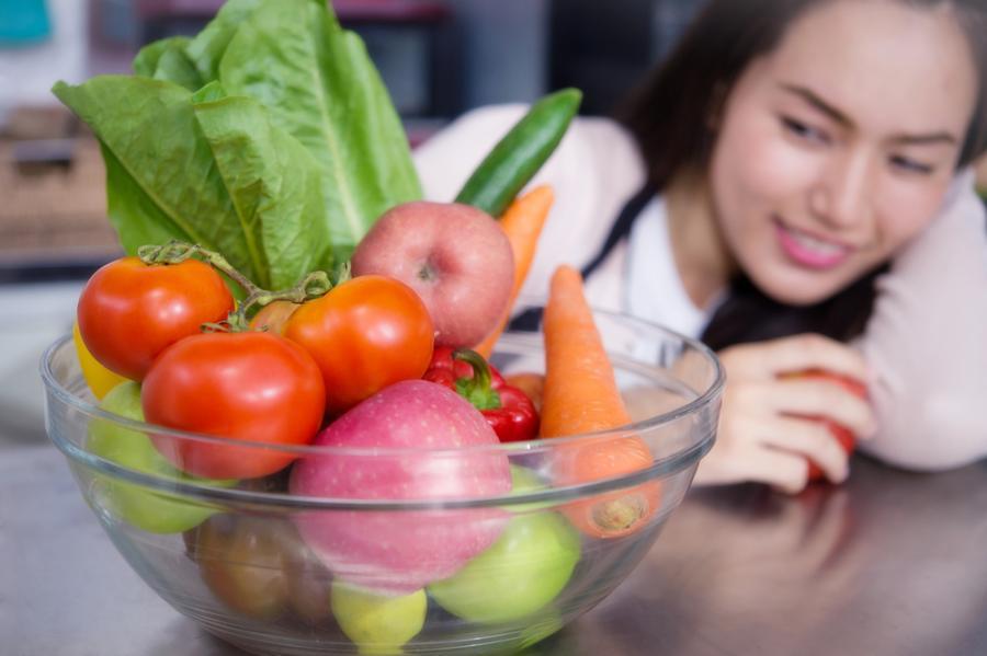 Kobieta przygląda się warzywom i owocom