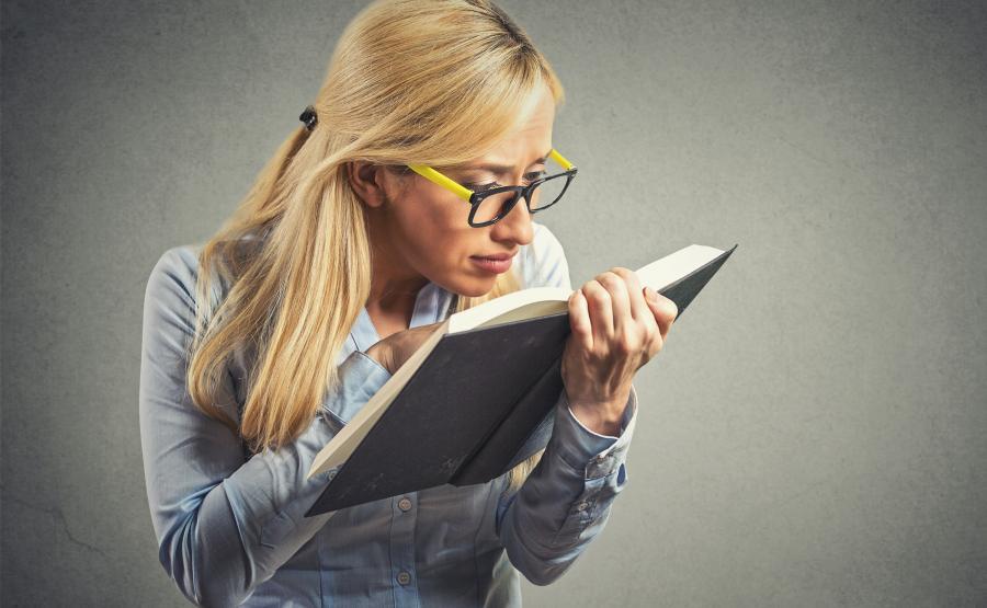 Kobieta w okularach czyta książkę