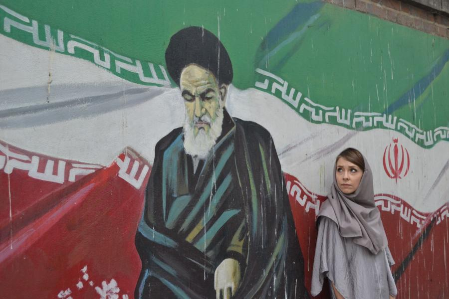 Aleksandra Chrobak w tradycyjnym irańskim hiżabie na tle muralu z wizerunkiem ajatollaha Chomeiniego