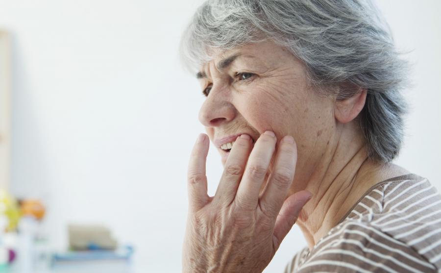 Starsza kobieta dotyka zęby