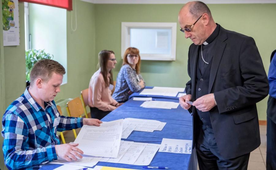 Prymas Polski abp Wojciech Polak (P) głosuje w lokalu wyborczym w budynku Szkoły Podstawowej nr 1 im. Zjazdu Gnieźnieńskiego w Gnieźnie