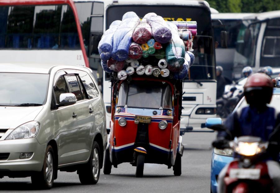 Przeładowana trójkołowa taksówka w Dżakarcie w Indonezji