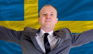 Biznesmen na tle szwedzkiej flagi