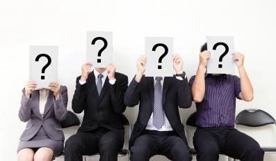 Ludzie zasłaniają twarze kartkami ze znakiem zapytania