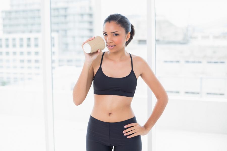 Kobieta pijąca kawę w czasie treningu fitness