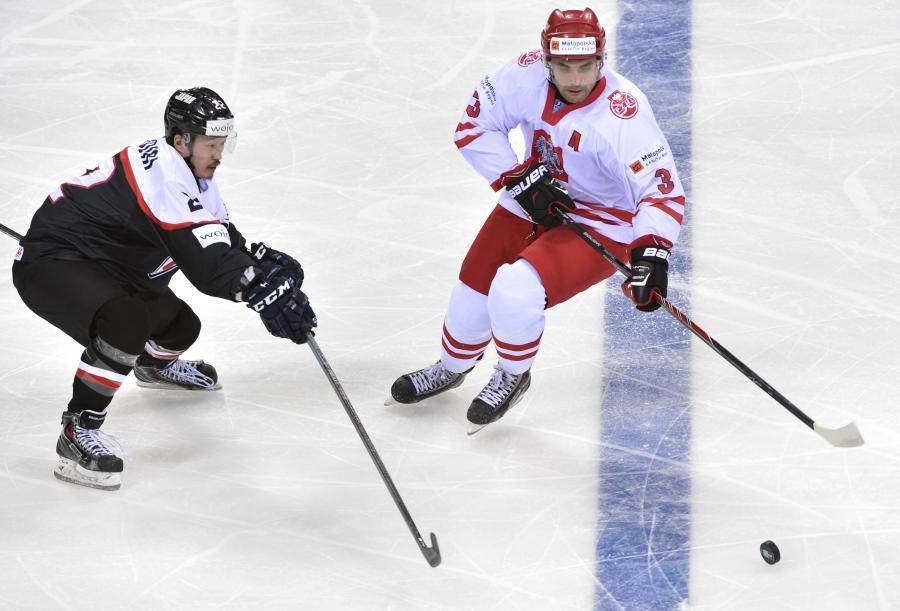 Polak Adam Bagński (P) walczy o krążek z Japończykiem Shinya Yanadori (L) podczas meczu hokejowych mistrzostw świata dywizji 1A w Krakowie