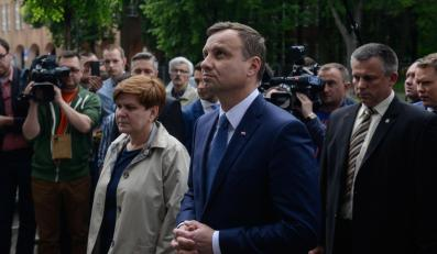 Andrzeja Duda (centrum-P) i szefowa jego sztabu wyborczego, wiceprezes PiS Beata Szydło (centrum-L) złożyli w Warszawie kwiaty pod tablicą upamiętniającą pomordowanych w okresie PRL
