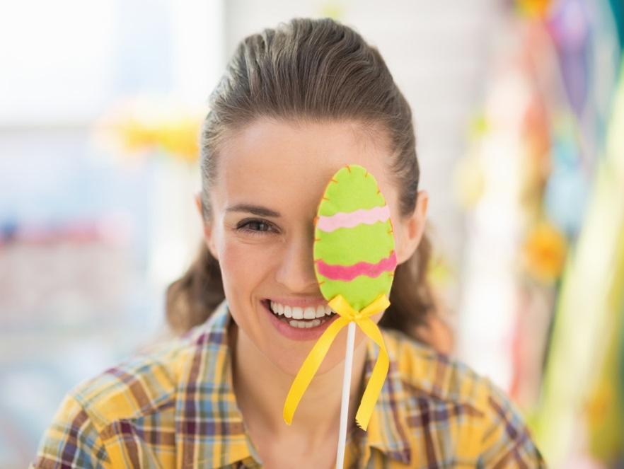 Kobieta zakrywająca twarz ozdobą wielkanocną
